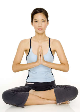 A pretty young asian woman in a meditative yoga pose photo