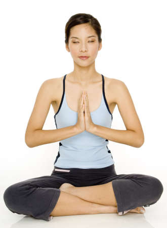 meditates: A young asian woman meditates with her eyes closed