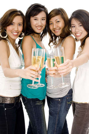 Four pretty young asian women celebrate in style with champagne photo