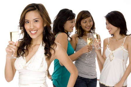 raises: A pretty young asian woman raises a glass of champagne with three friends talking in background
