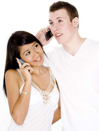 A young couple are both talking on mobile telephones photo