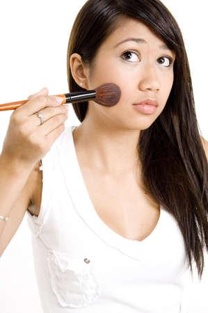 mujer maquillandose: Un atractivo joven mujer asian aplicar maquillaje a su mejilla con un pincel  Foto de archivo
