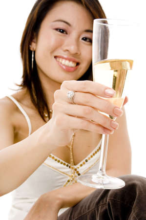 A young asian woman lifts her glass of champagne for a toast (focus is on the glass) photo