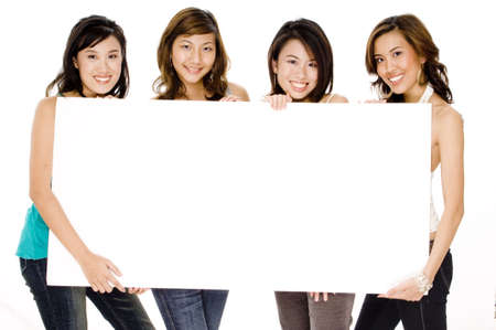 Four attractive young asian women holding a blank sign board