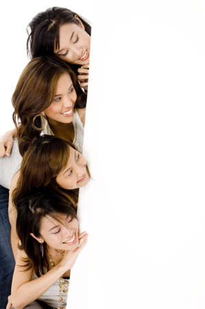 Four attractive young asian women looking at a verical sign (blank)