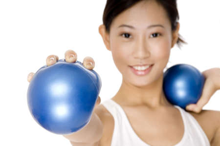 resistance: A young asian woman holds a small resistance ball towards the camera (focus on ball) Stock Photo