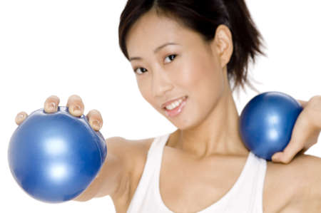 A smiling young asian woman working out with small medicine balls
