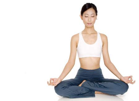 relaxes: Una joven mujer asian relaja con los ojos cerrados en un yoga plantean