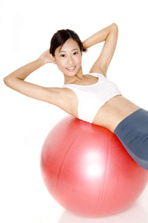crunch: A slim young asian model does a crunch on a red fitball