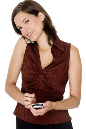 A young businesswoman makes notes on her PDA whilst on the phone Stock Photo - 530510