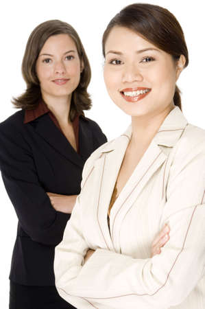 A smiling asian businesswoman (in focus) stands in front of her western colleague