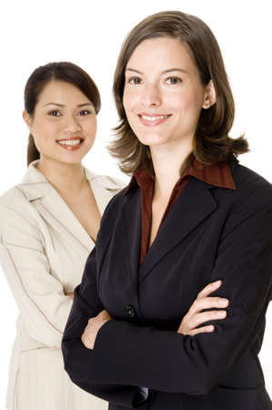 A smiling young businesswoman stands in front of her colleague