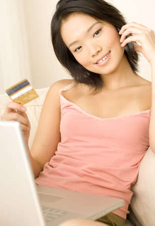 A young asian woman enjoying shopping online with gold credit card (shallow depth of field used) Stock Photo - 541571