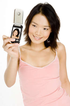A pretty young asian woman takes her picture using her phone photo