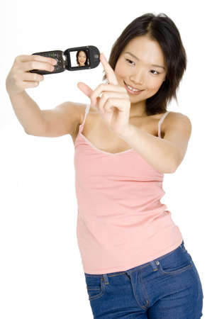 An attractive young asian woman taking her picture with a camera phone photo