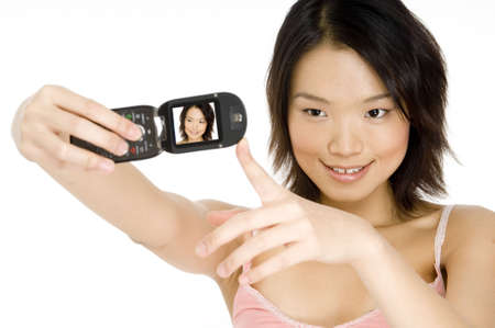 A pretty young asian woman takes her photo with her camera phone photo