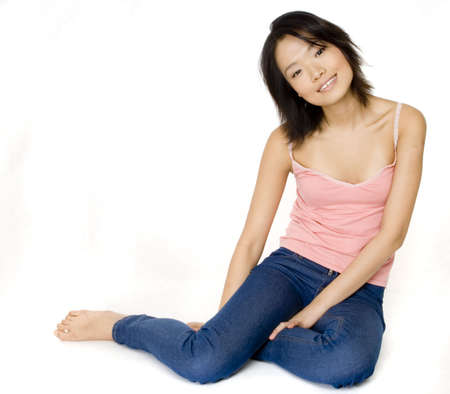 A young asian woman sitting on the floor isolated on white photo