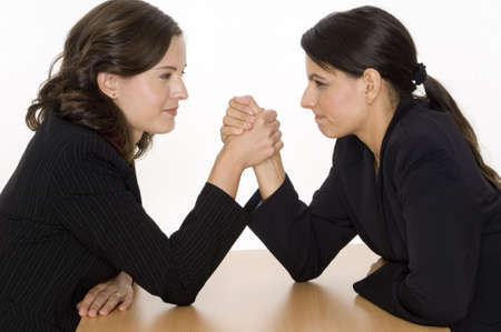 Two women arm wrestling at work on desk on white background photo