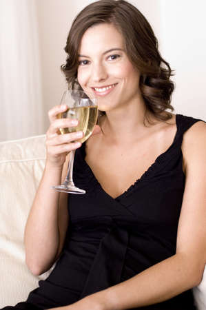 A young woman relaxes at home on the sofa with a glass of white wine (shallow depth of field used) photo