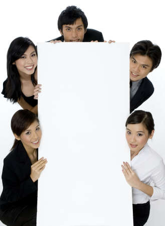 Five young asian businessmena and women holding a large blank sign Stock Photo
