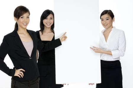 A young attractive businesswoman points to a blank sign which is being held up by her two attractive colleagues