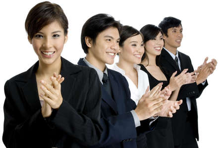 A team leader applauds at the camera whilst her team applauds behind her Stock Photo