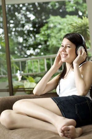A young attractive woman wearing headphones listens to music sat at home on the sofa Stock Photo - 587290