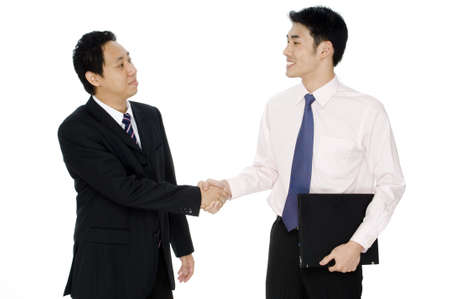 conclude: Two asian businessmen shake hands and conclude a business deal on white background