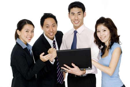 Cuatro jóvenes hombres de negocios asiáticos y las mujeres con un ordenador portátil