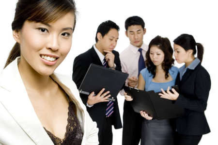 A beautiful young asian businesswoman standing in front of a working business group on white background Stock Photo