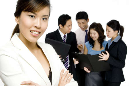 An attractive businesswoman standing in front of a working business team on white background