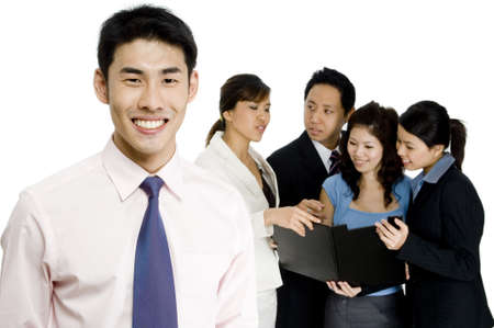 asian business women: A smiling businessman standing in front of a small business team on white background Stock Photo