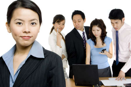 A young asian businesswoman standing in front of a working business team on white background Stock Photo - 683174