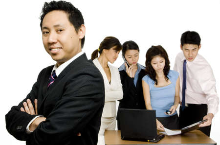 A young enthusiastic businessman standing in front of a group of colleagues who are working