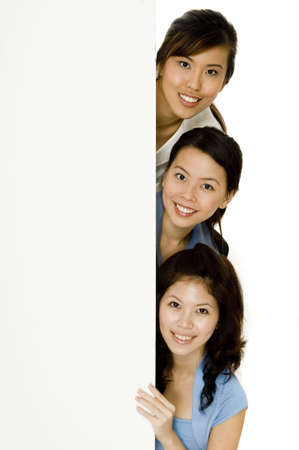 Three young attractive asian women with a vertical blank sign for a message Stock Photo