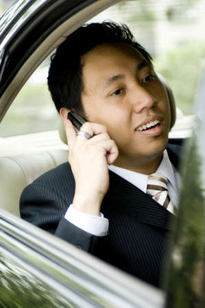 A young business executive making a phone call in the back seat of a car photo