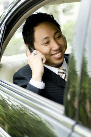 driven: A young asian businessman making a business call in the back of a car