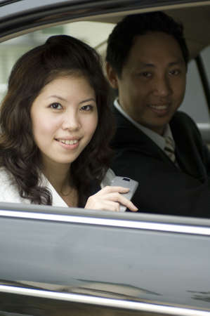 A young businesswoman sitting in the back of a car with her male colleague photo