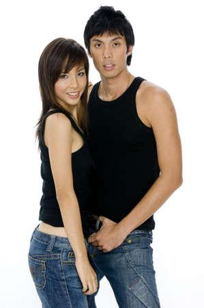 bloke: Una donna asiatica attraente giovane con le parti superiori nere da portare asiatiche alte che i jeans delluomo sia su priorit� bassa bianca