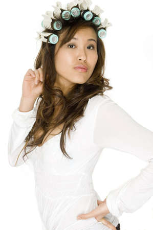 An attractive Asian woman in rollers having hair styled on white background photo