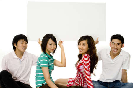Four young asian adults sitting on the floor and holding up a blank sign Stock Photo