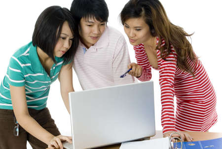 causal: Three asian students study at a desk with folder and laptop Stock Photo