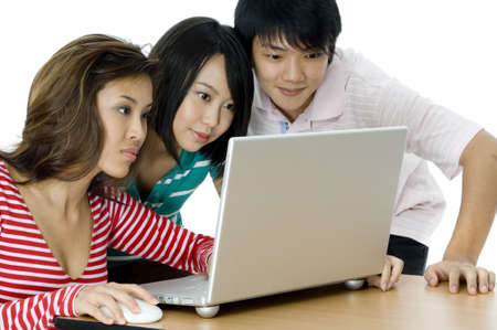 causal: Three young asian adults looking at a laptop computer on white background