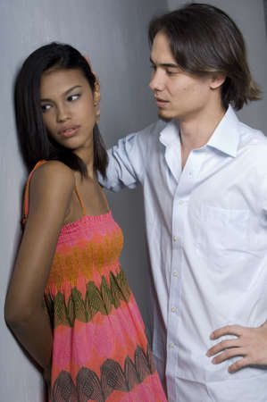 sulk: A young woman leaning against a wall looking away from her boyfriend Stock Photo