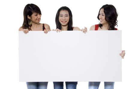 Tres muchachas adolescentes bonitas que llevan a cabo una muestra en blanco en el fondo blanco Foto de archivo - 765637