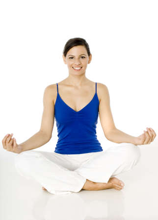 A young woman sitting on the floor in a yoga position on white background Stock Photo
