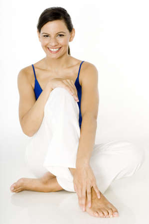 A young woman sitting on floor with great smile on white background