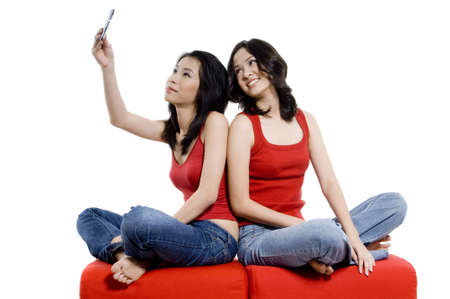 A young woman takes a picture of herself and her friend using mobile phone