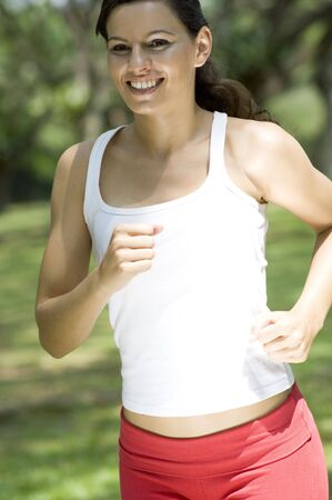 A beautiful young woman running in the park photo