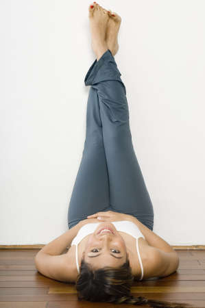 A young woman with her legs up against the wall looking back at the camera